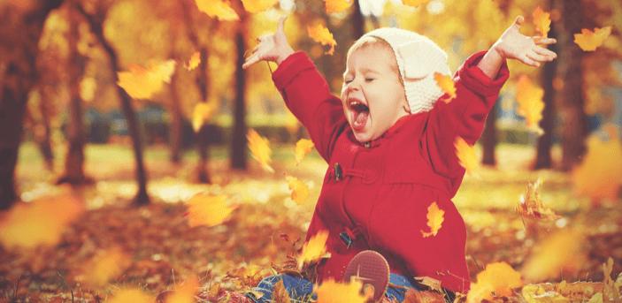 落ち葉を舞い上げ喜ぶ子供
