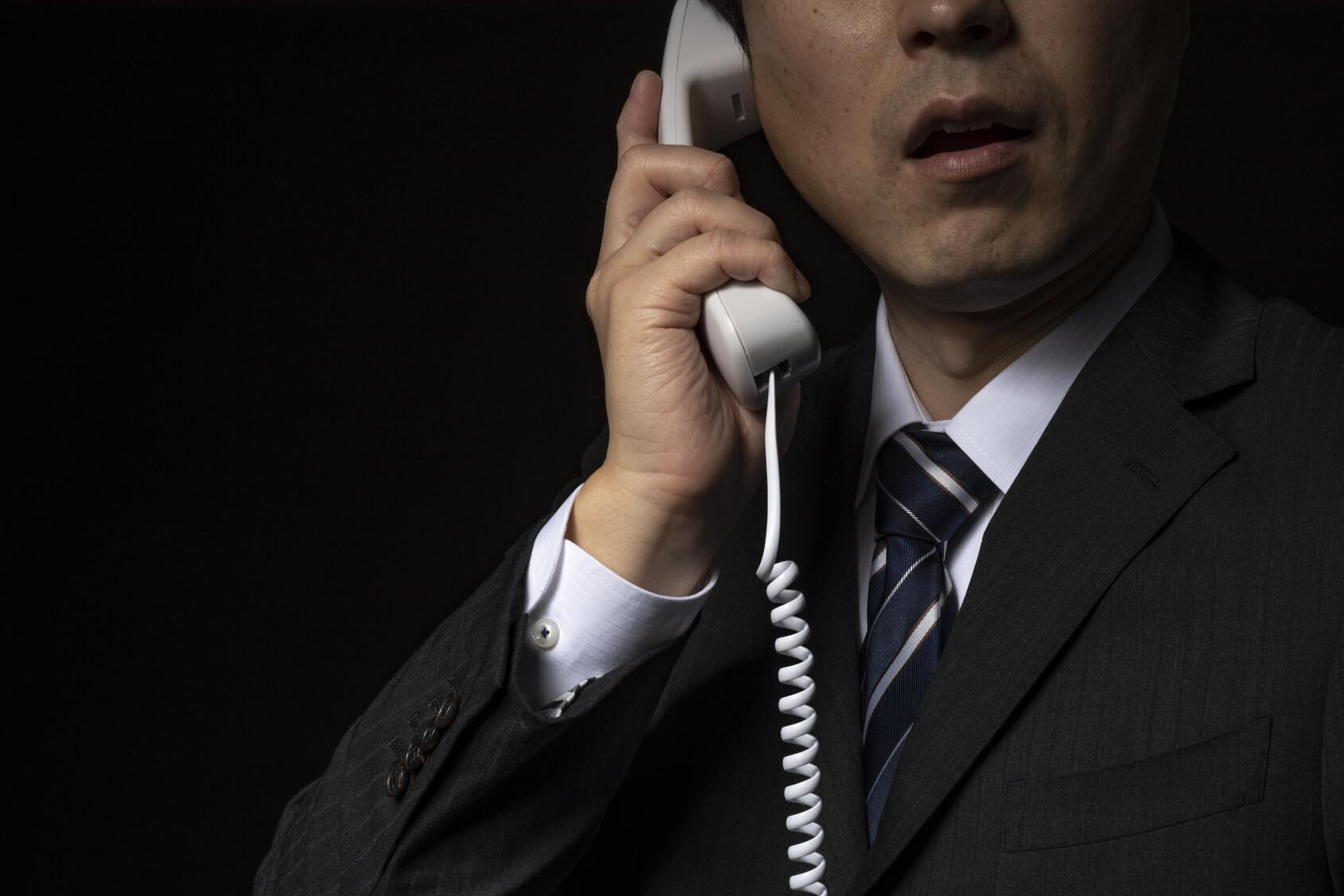 電話で話をするスーツの男性